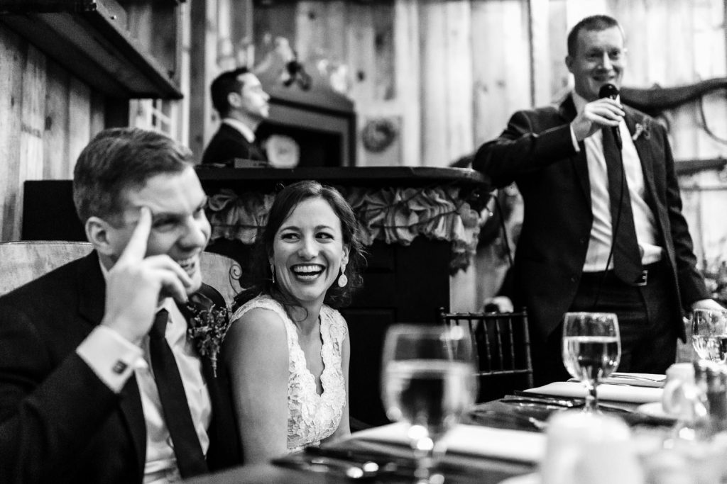 A bride and groom laugh during the best man speech at their wedding
