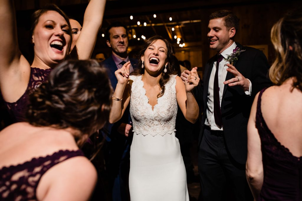A bride dances with joy at her five bridge inn wedding