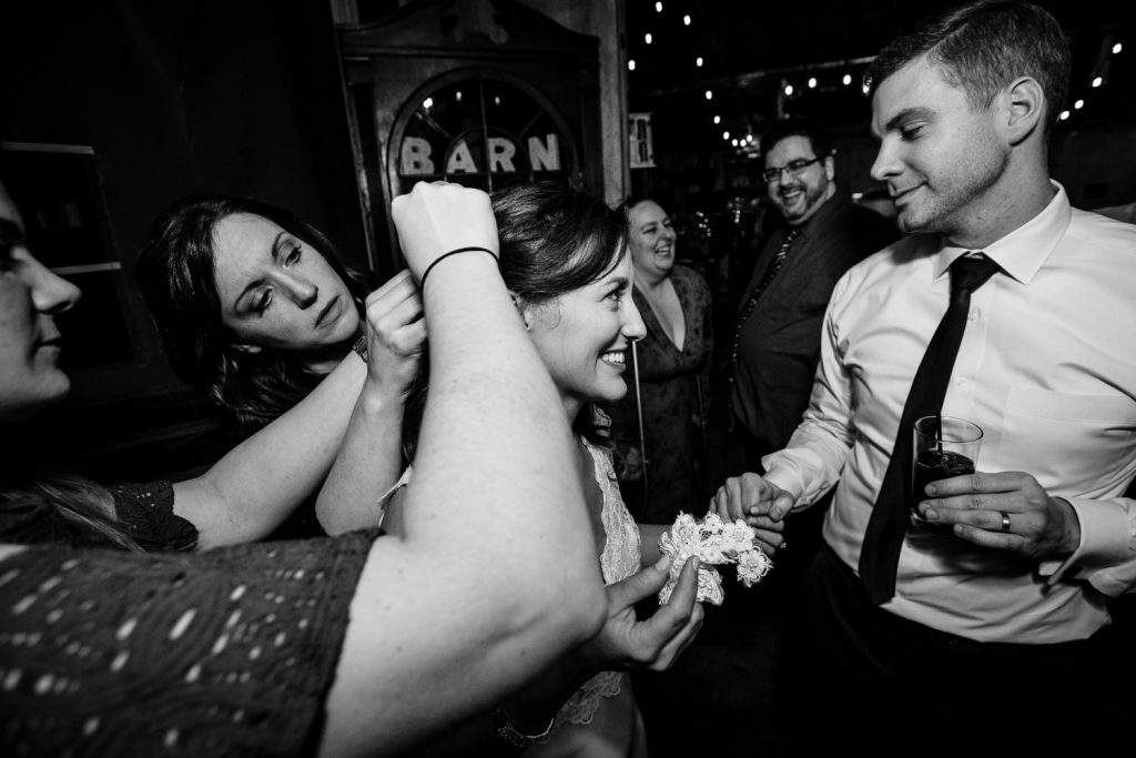 Two women help a bride fix her hair while she shares a moment with her groom