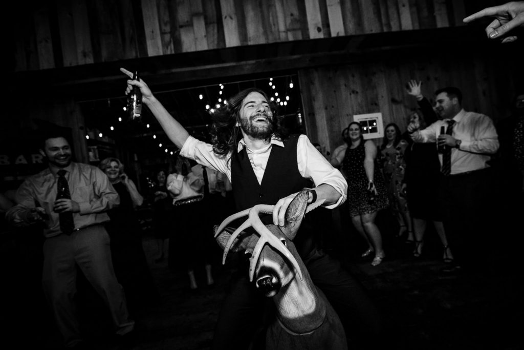 A wedding guest rides a plastic deer at a barn wedding