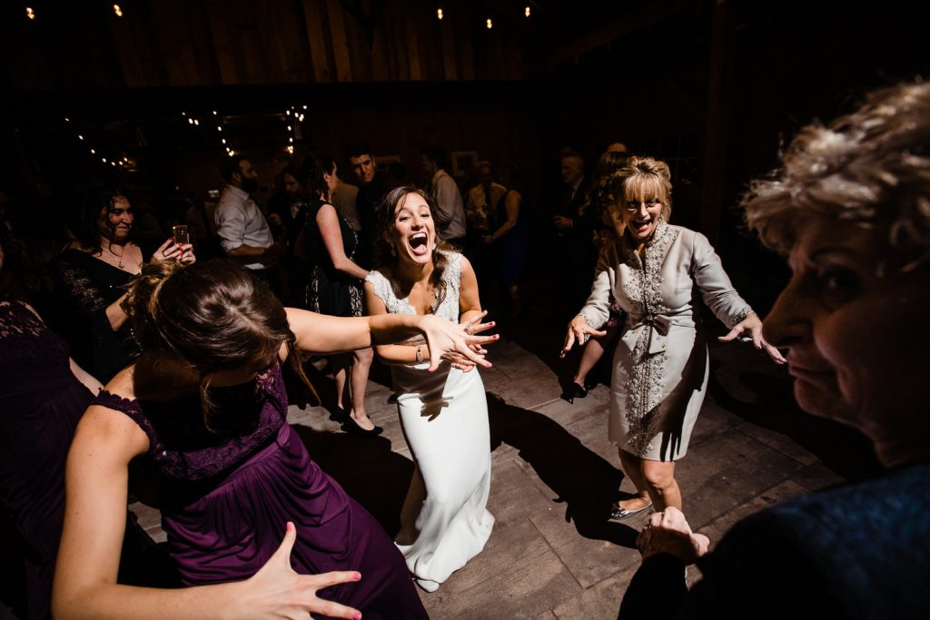 A bride dancing with her mom and grandma at her wedding