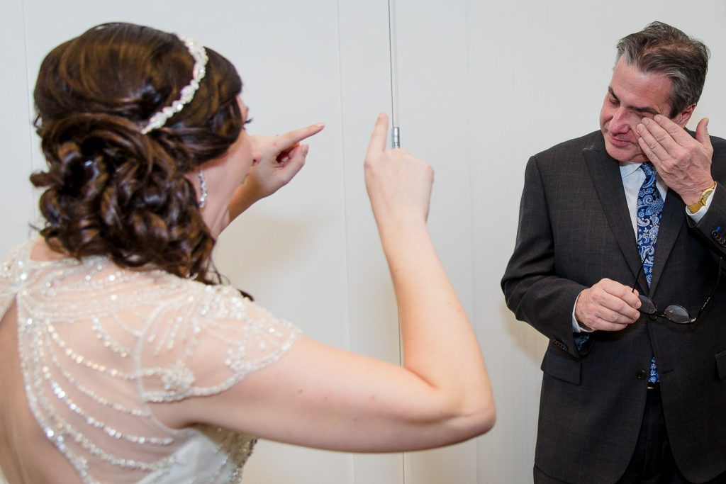 A bride points out her fathers tears after he sees her in her wedding dress