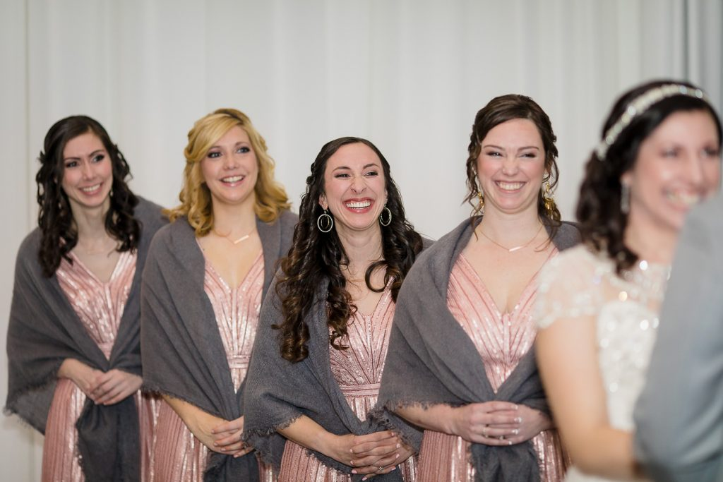 Bridesmaids smile and laugh during the wedding ceremony