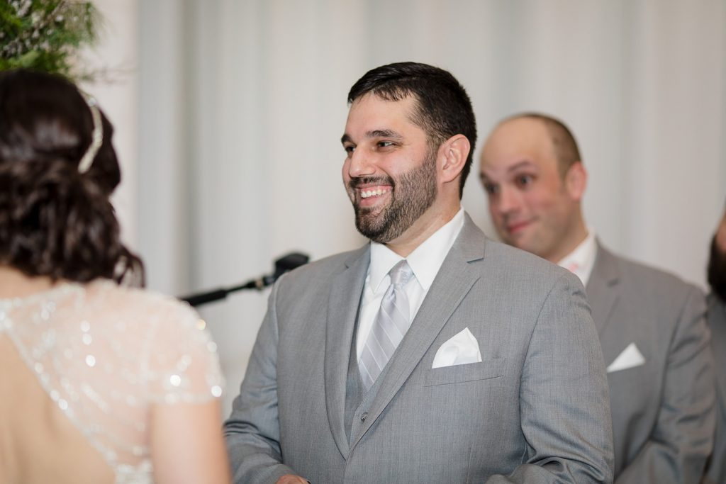 A groom smiles as he reads vows to his soon to be wife
