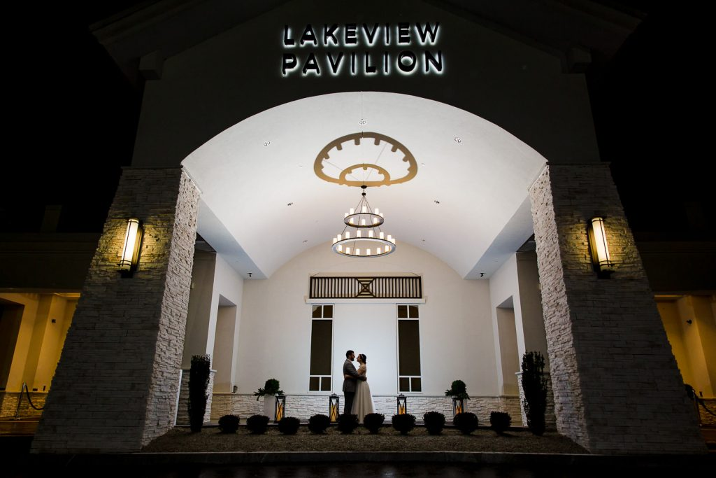 A silhouette wedding photo of a bride and groom face to face outside lakeview pavilion