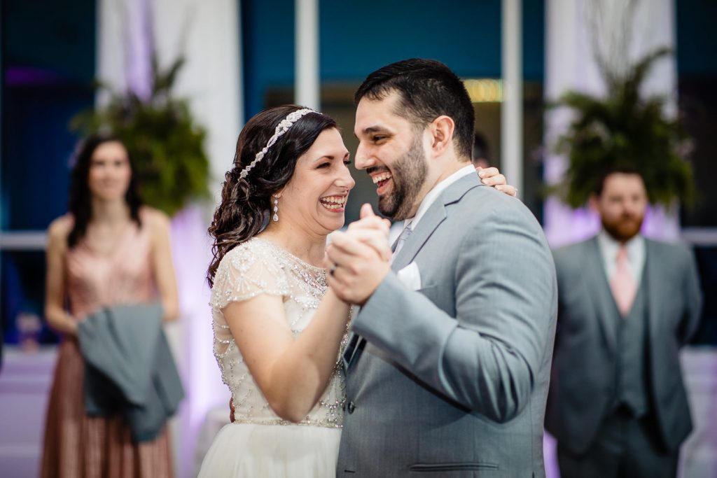 A bride and groom smile and laugh during their first dance at their lakeview pavilion wedding