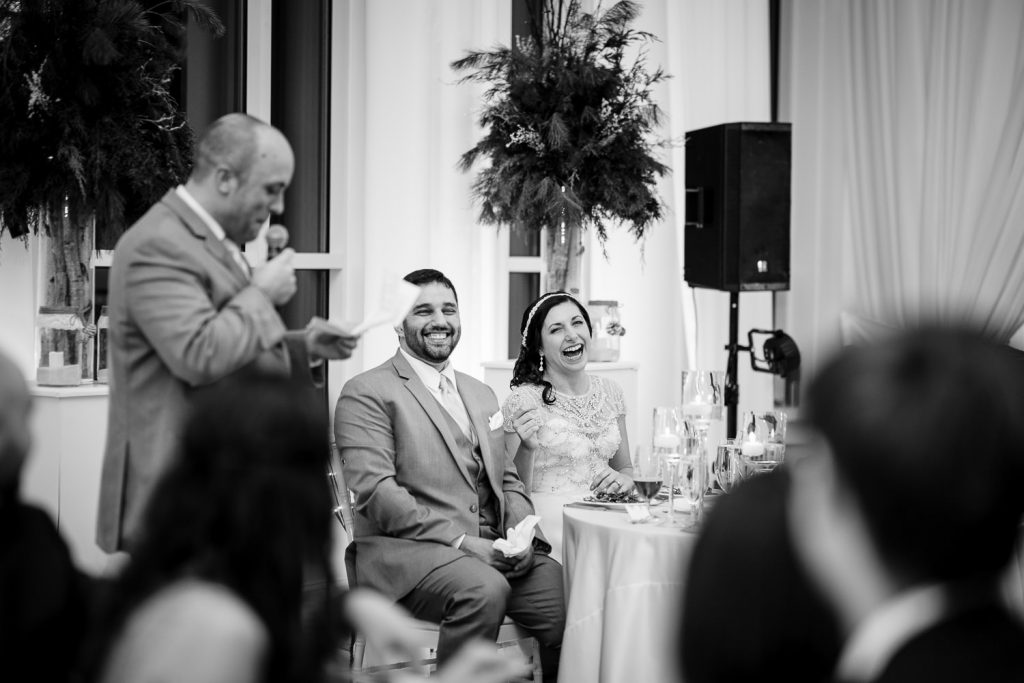 A bride and groom laugh at their sweetheart table as the speeches are read