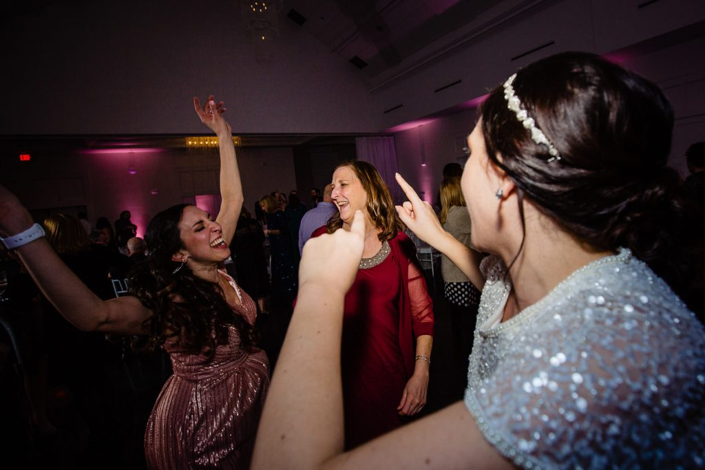 A bride dances with friends at her wedding reception