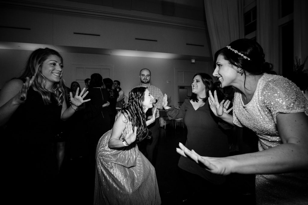 A bride and friends dance with jazz hands at her wedding