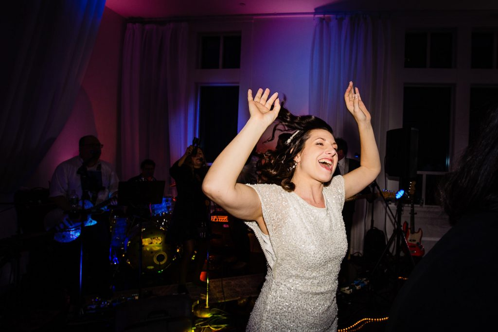 A bride dances with her arms up through her reception at lakeview pavilion