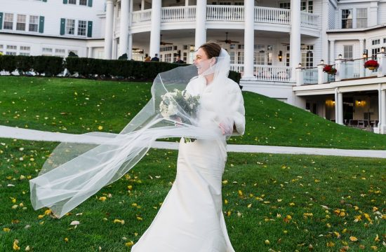 Bride's veil blows in the wind in front of sagamore resort wedding on lake george