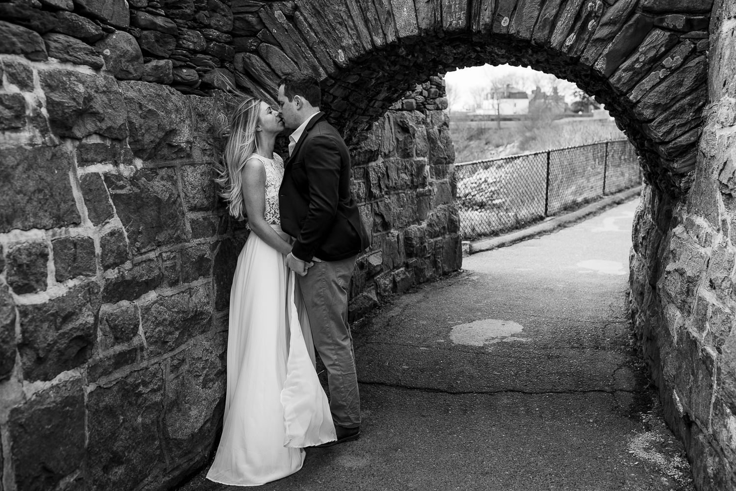A couple kisses beneath one of the stone tunnels along cliff walk during their newport rhode island engagement session