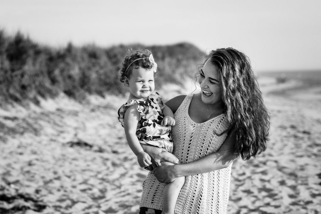 A girl laughs while holding her infant cousin on the beach in cape cod