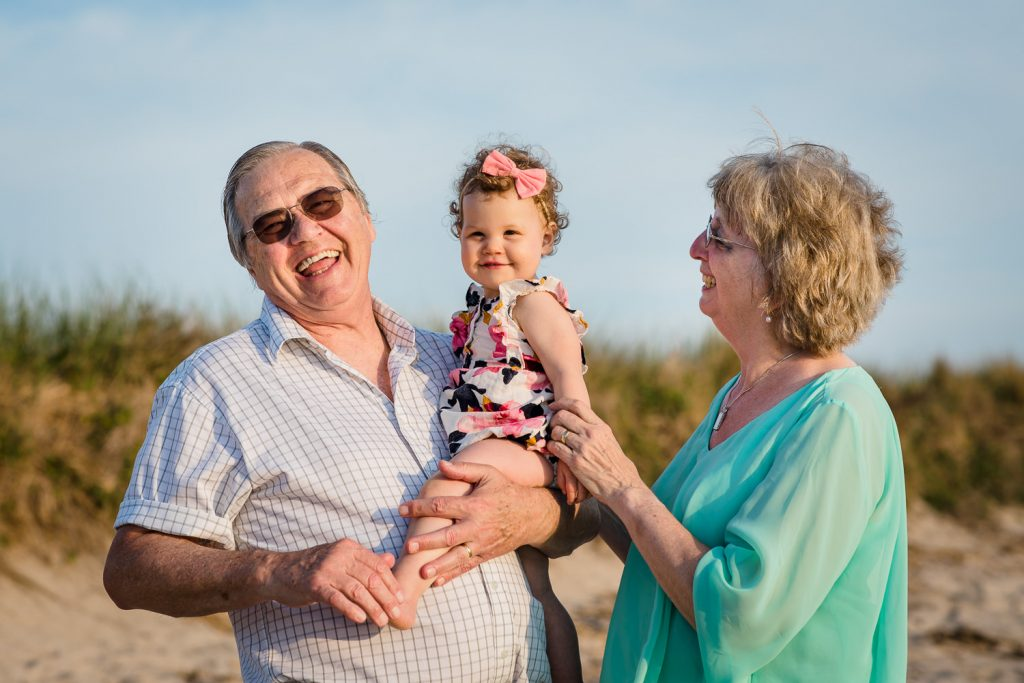 A grandmother and grandfather play with their infant grandaughter on the beach in wellfleet