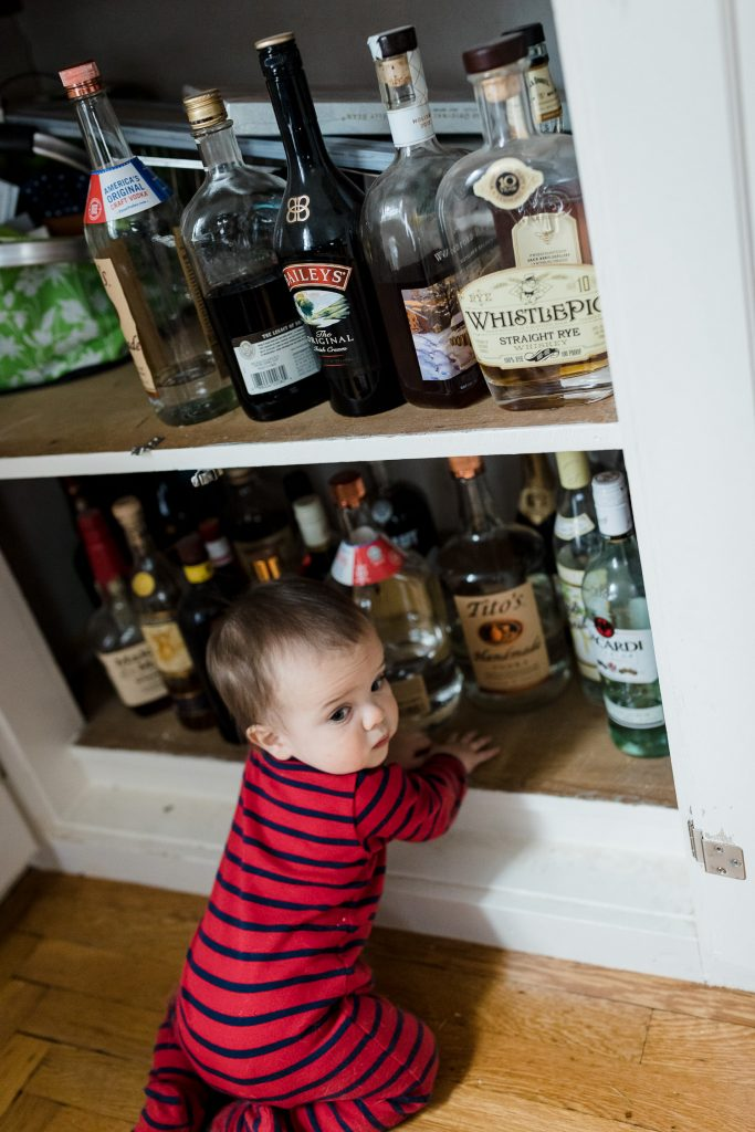 Little boy in red pajamas gets into parents liquor cabinet during rhode island photo session