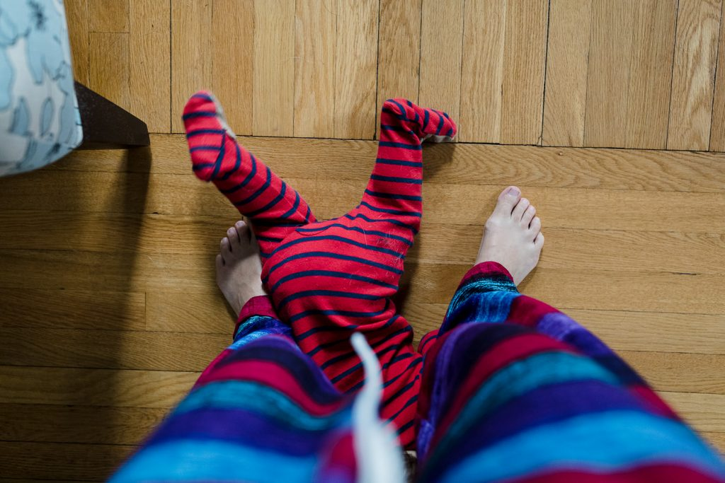 Baby legs in red striped pajamas stick out from parents legs during at home family photo shoot in rhode island