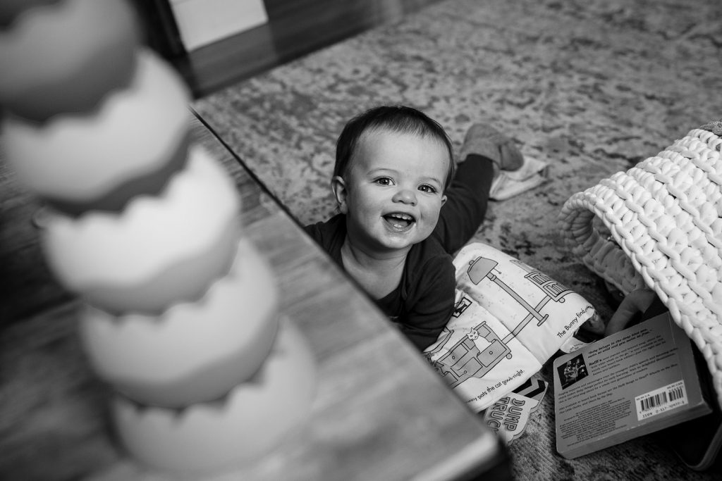 Little boy has a big smile from a floor filled with toys in rhode island family photo session