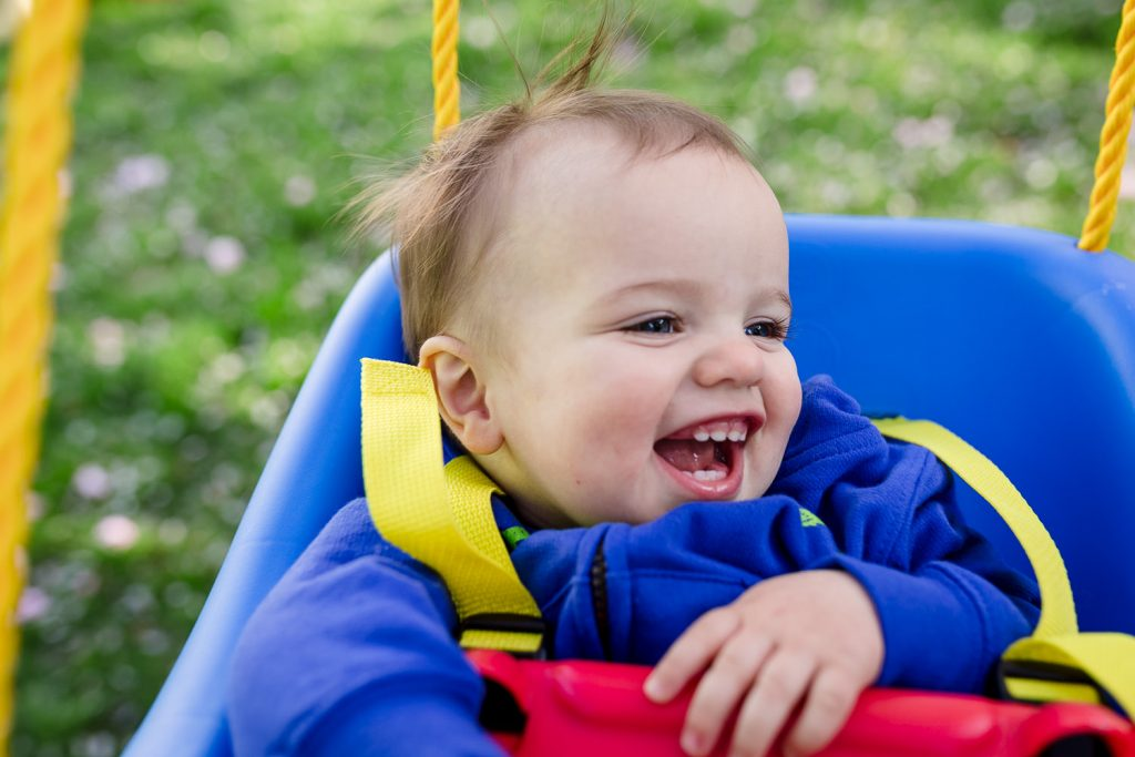 Little boy laughs while swinging in little tykes secure swing during east greenwich rhode island family photos
