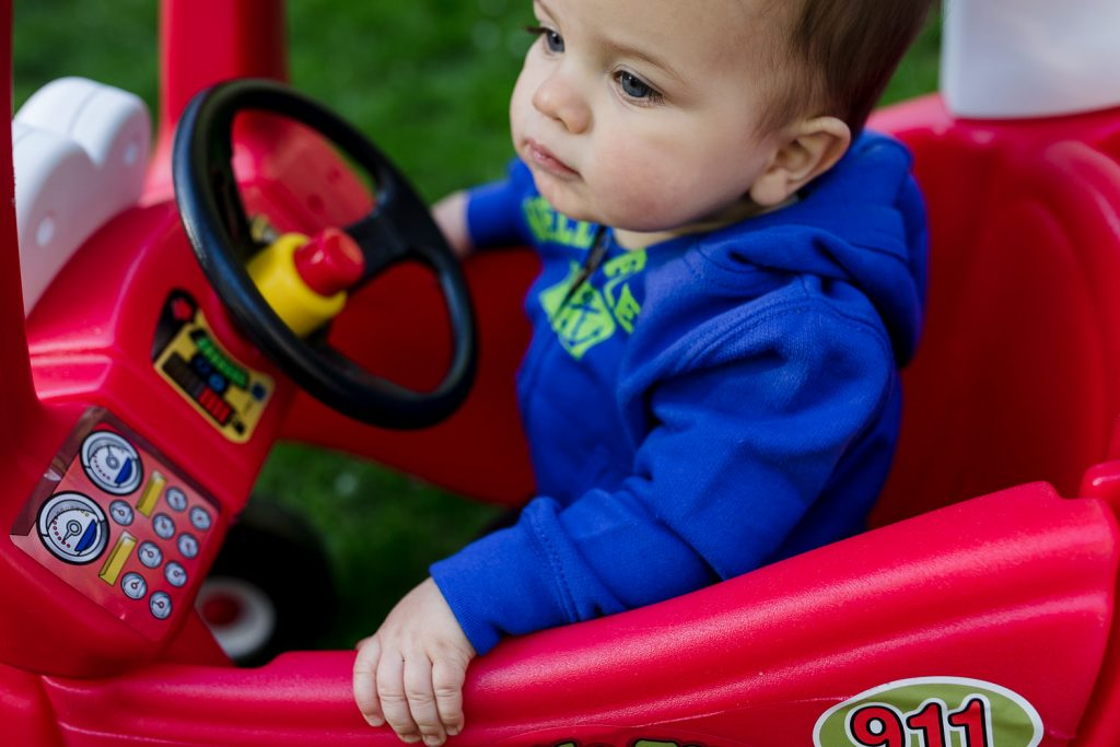 A seriously toddler boy in blue sweatshirt sits in a red Little Tykes cozy coupe during rhode island photos