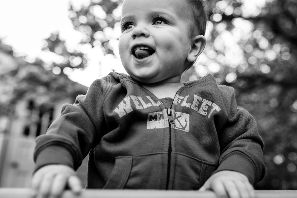 Black and white photo of little boy in Wellfleet sweatshirt sticking tongue out during rhode island family session