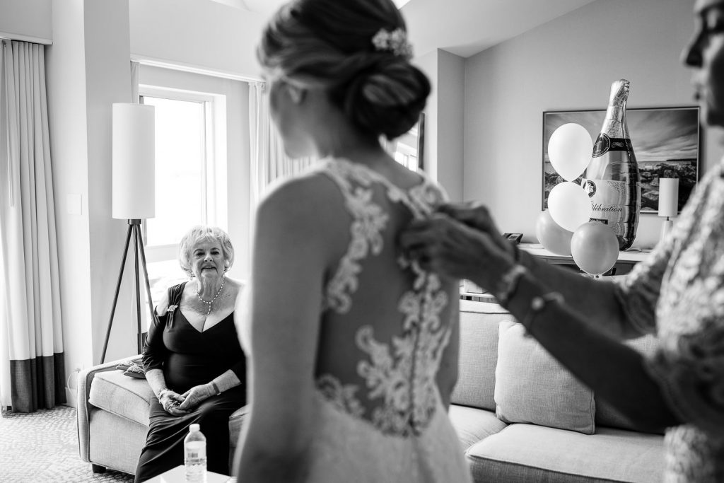 The mother of the groom looks on as the mother of the bride helps the bride into her dress
