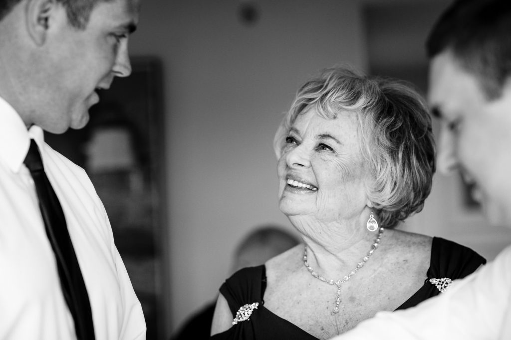 The mother of the groom looks lovingly at her son and his best friend getting ready for the wedding