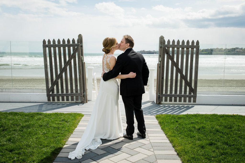 A bride and groom kiss on the walkway to the beach at Newport Beach House