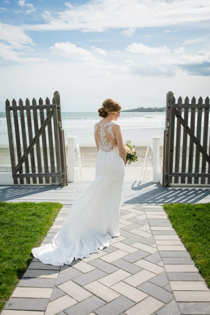 A bride's dress floats in the wind as she poses by the beach in newport ri