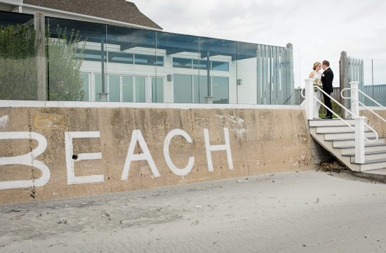 A bride and groom stand at the top of a set of stairs leading to the beach with the word BEACH written on the sea wall in front of their wedding at the Newport Beach House in Middletown, RI