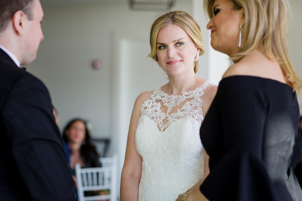 The bride listens to the wedding officiant during her wedding ceremony at Newport Beach House