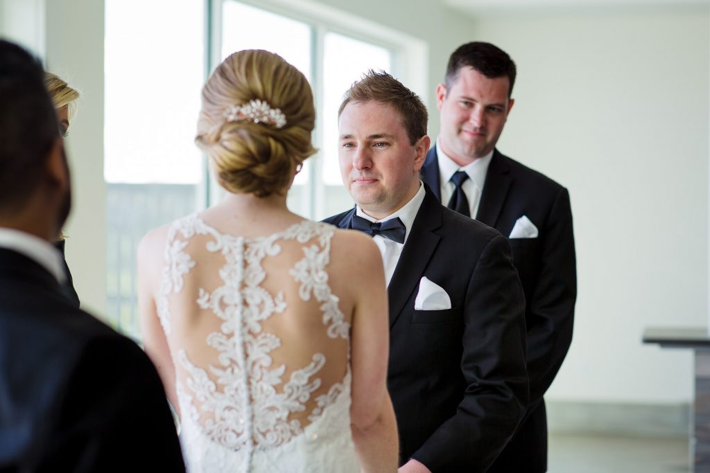 The best man looks on as the groom says his vows