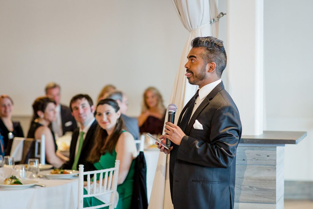 The best man makes a funny face while delivering his wedding speech