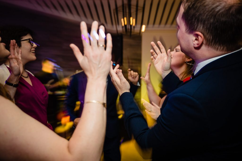 Guests clap their hands while dancing at a wedding reception