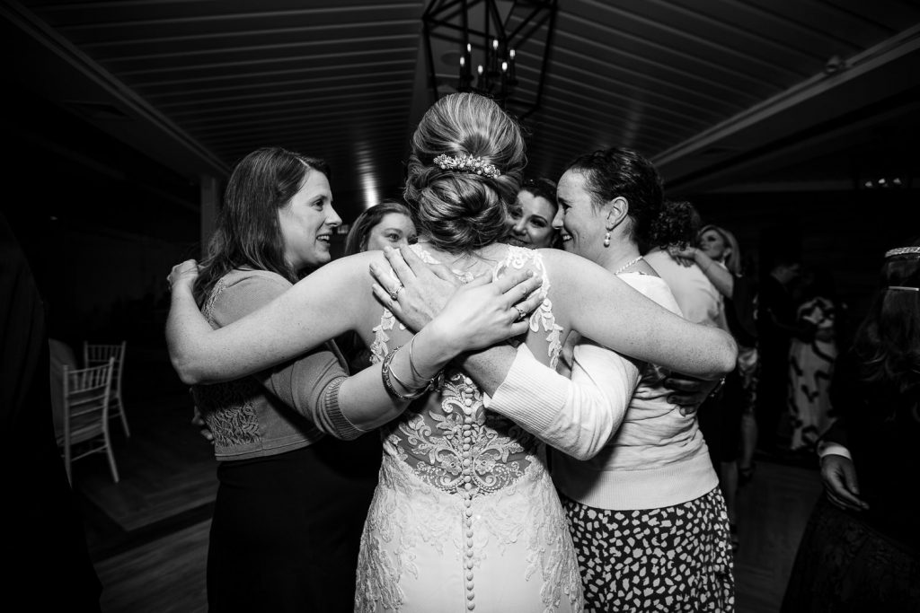 The bride dances in a circle with her arms around her close childhood friends
