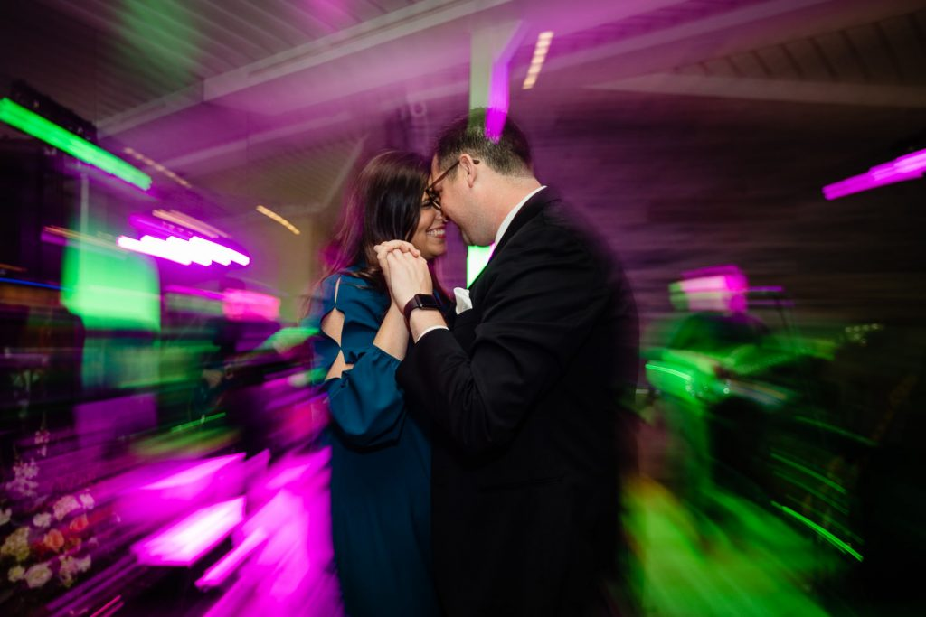 A wedding guest couple dance amidst the neon lights of the wedding band