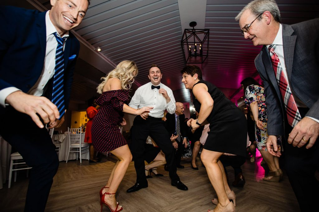 A bunch of guests dance with the groom at his Newport Beach House Wedding