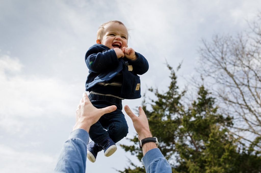 Flying baby boy in blue pea coat and jeans during rhode island family photos session