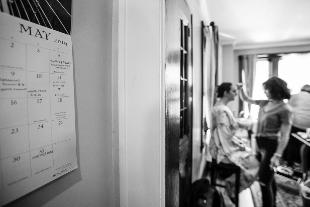 A calendar showing the couples wedding date hangs on the wall while the bride gets her makeup done in the next room