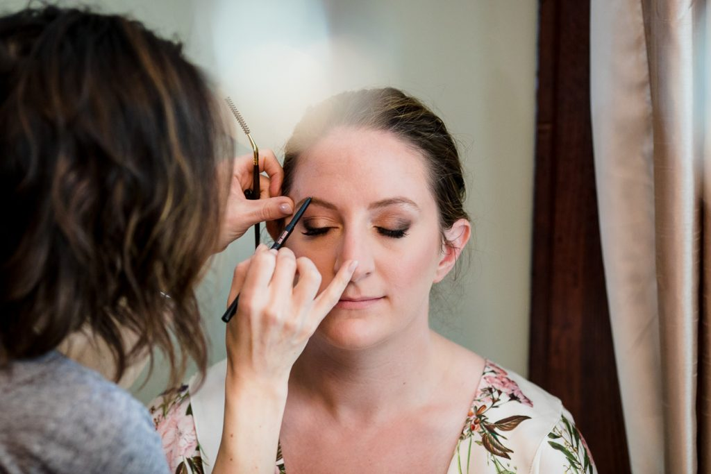 The bride gets her eye makeup applied