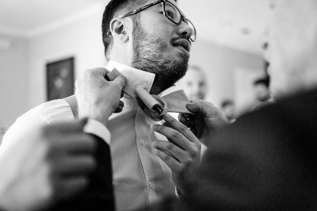 A groom gets help tying a bowtie for his wedding