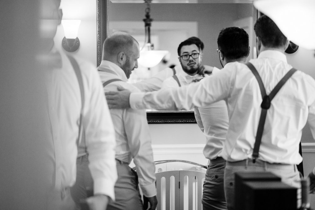 A groom looks in the mirror as he is getting ready for his wedding
