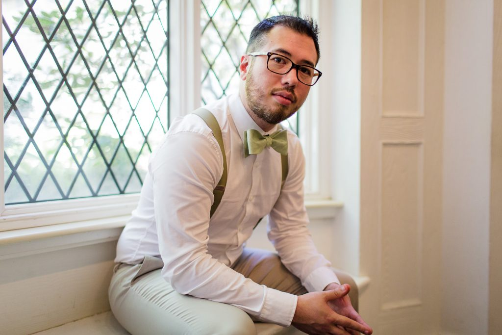 A groom sits pensively in the bendel mansion at stamford nature center