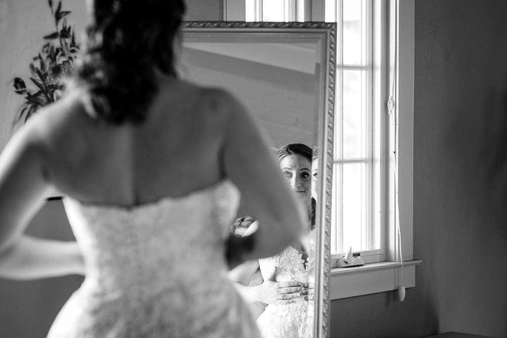 A bride looks at herself in the mirror