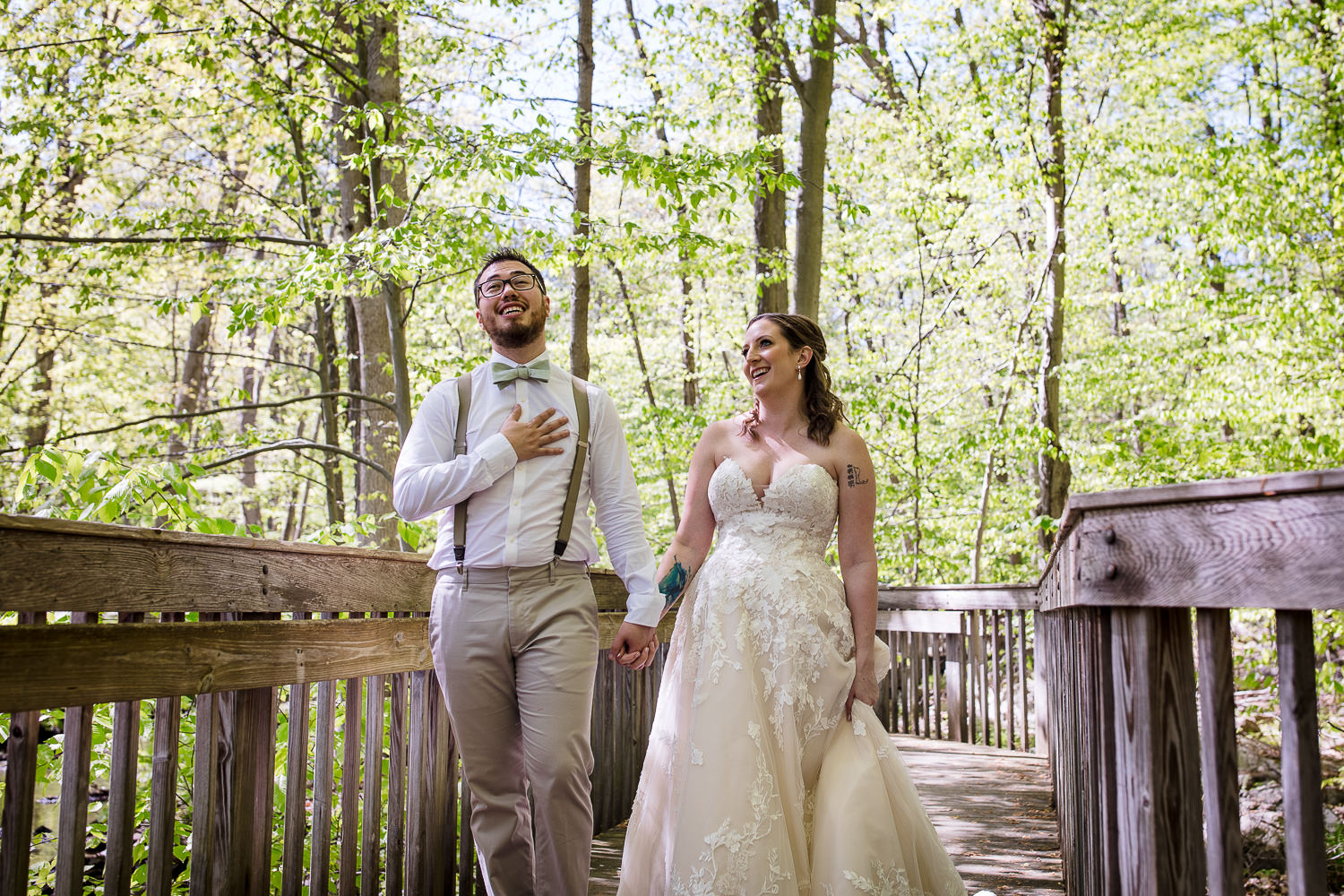 A bride and groom walking in the woods at their Stamford Nature Center wedding in Fairfield County, Connecticut.