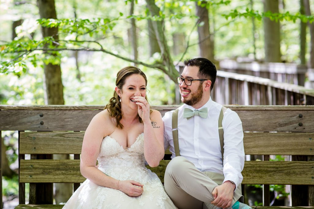 A bride and groom laugh on a bench in the stamford nature center wheels in the woods trail
