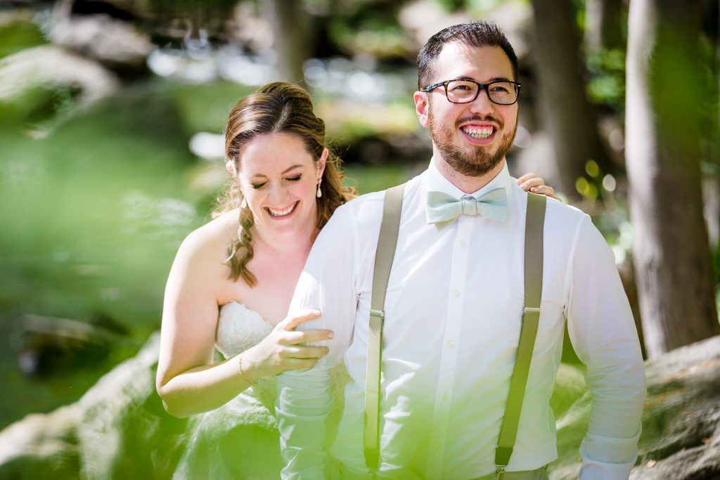 A bride and groom laugh during wedding portraits at the stamford museum and nature center wedding