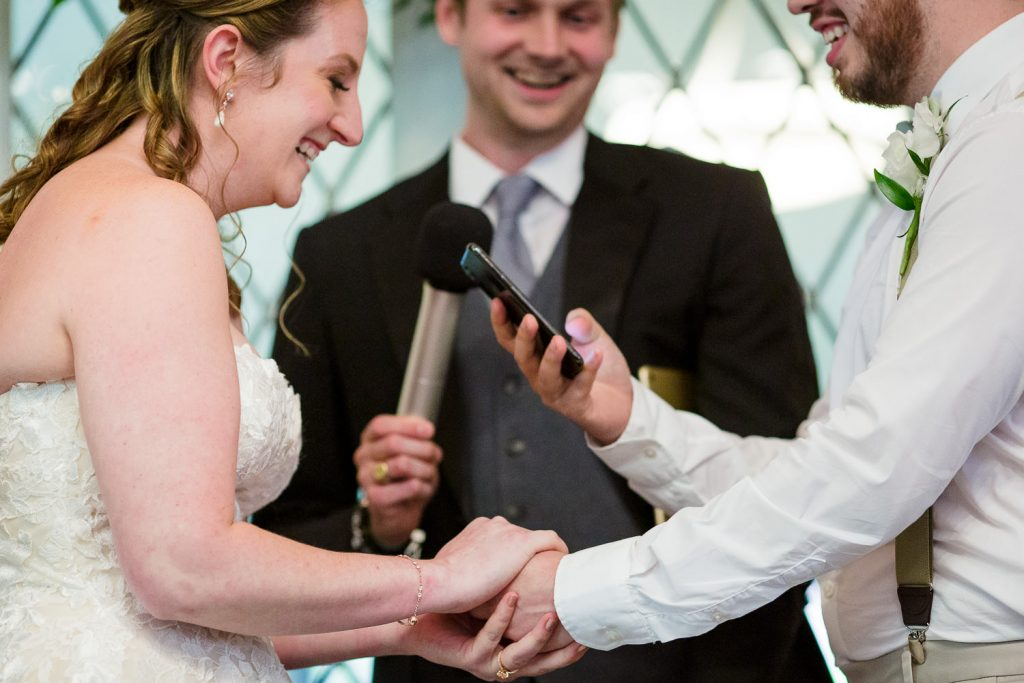 A bride and groom laugh hysterically during their wedding vows
