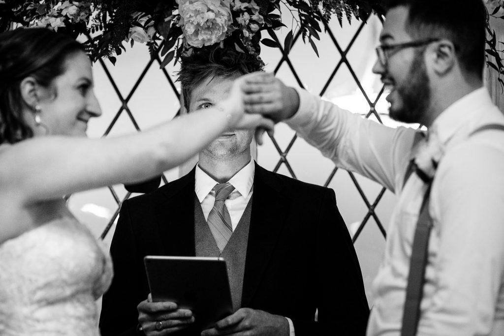 A bride and groom do a secret handshake during their wedding ceremony
