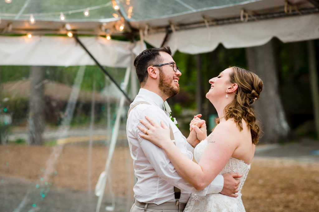 The bride and groom share a first dance under a clear tent at stamford nature center