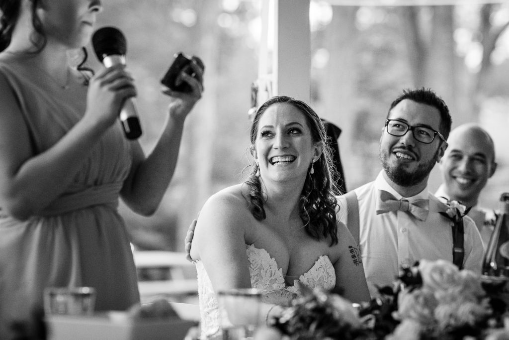 The bride and groom laugh as the maid of honor gives her speach
